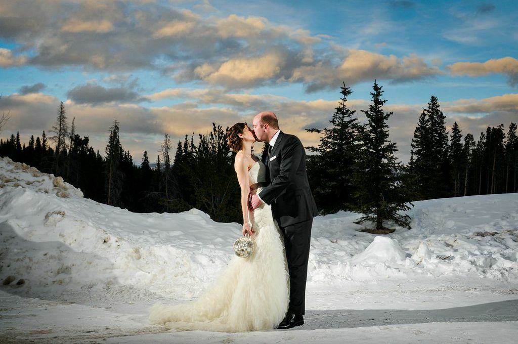 Wedding Picture Of A Bride And Groom Kissing In The Snow